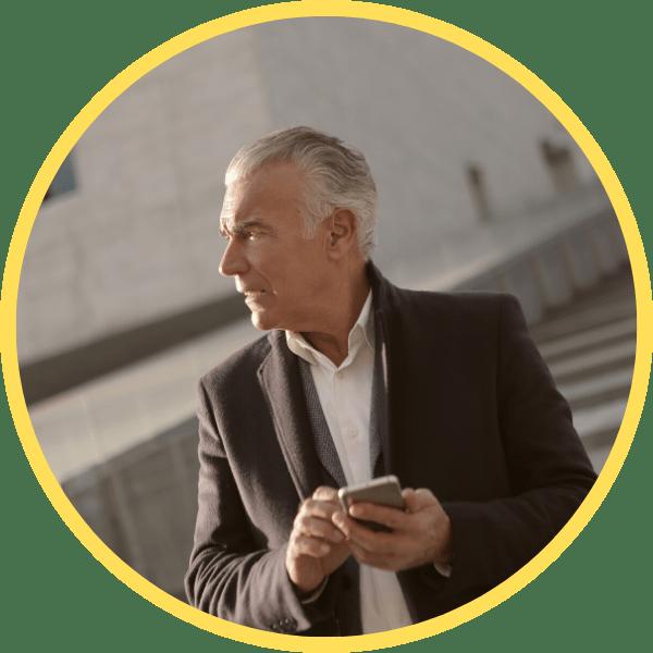 Mann mit Handy ruft die ESM Experten von Servisation an vor grauer Treppe