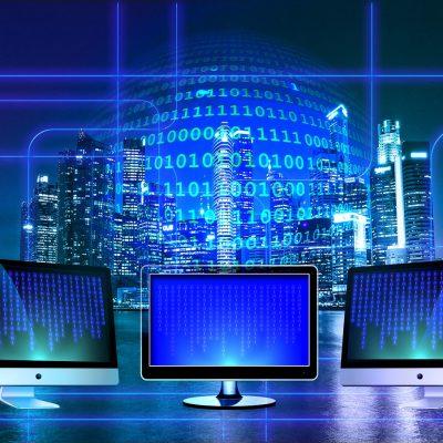 Digitalisierung symbolisiert durch drei Computer, die vor einer Skyline stehen